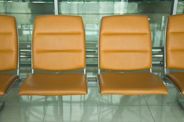 row of orange chair at airport