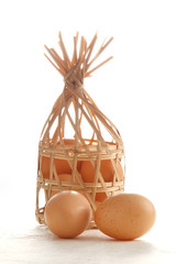 egg in wooden basket on white paper