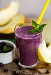 Blueberry smoothie in a glass with a straw and sprig of mint, ov