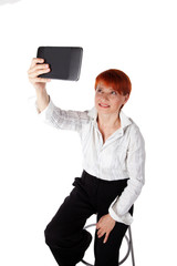 beautiful elderly woman photographs a tablet