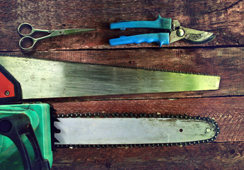 Garden tools on a wooden background. Saws and secateurs.