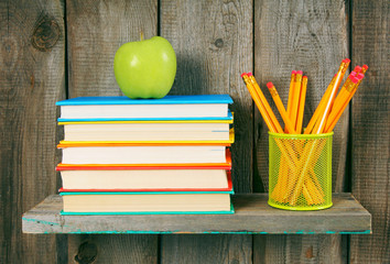 Apple, pencils and books on a wooden shelf.
