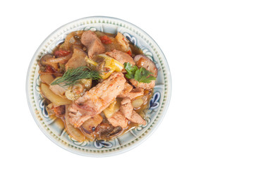 meat stew with vegetables and herbs in a bowl isolated on white