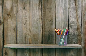 Pencils on a wooden shelf.