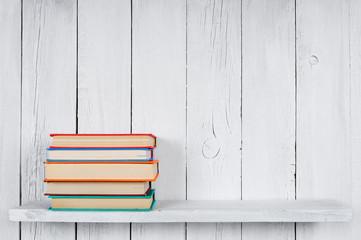 Books on a wooden shelf.