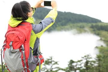 woman hiker in emei mountain taking photo with smart phone