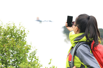 woman hiker in emei mountain taking photo with smart phone