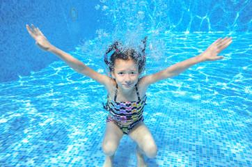 Happy active underwater child swims in pool, kids sport