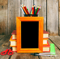 Books and school tools on wooden background.