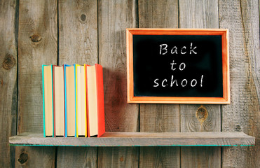Back to school. Books on wooden shelf and frame.