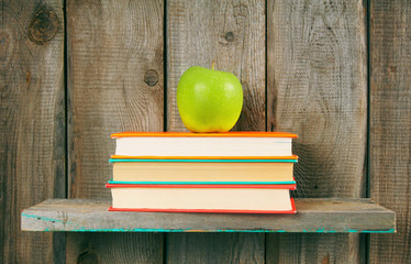 Apple and books on a wooden shelf.