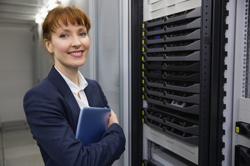 Pretty technician smiling at camera beside server