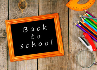 Frame and school tools. Vertically. Wooden background.