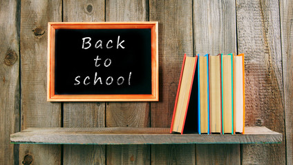 Back to school. Books on wooden background.