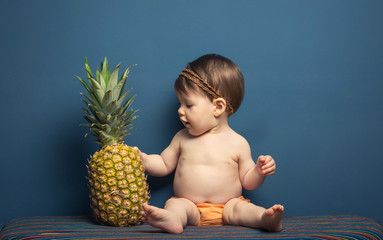 Happy baby girl playing with a pineapple