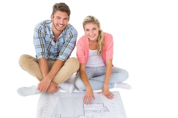 Attractive young couple sitting looking at blueprint