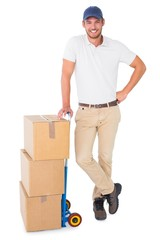 Happy delivery man leaning on trolley of boxes