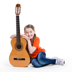 Cute girl sitting with acoustic guitar.