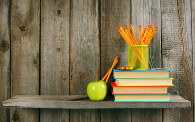 Books, apple and pencils on a wooden shelf.