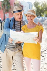 Happy tourist couple using map in the city
