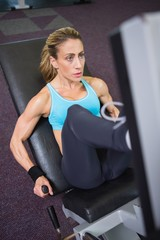 Fit young woman doing leg presses in gym