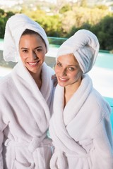 Smiling young women in bathrobes
