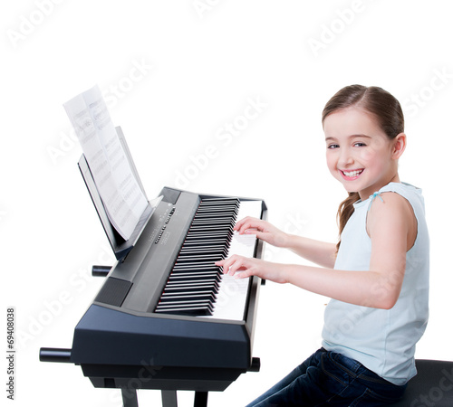 canvas print picture Smiling girl plays on the electric piano.