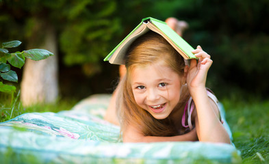 Little girl is hiding under book outdoors