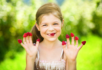 Young girl is holding raspberries on her fingers