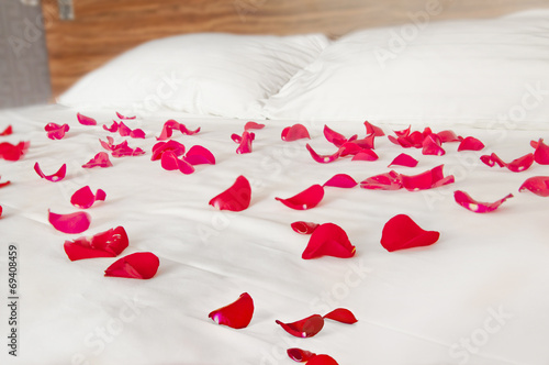 canvas print picture Rose petals on white bedding - romantic bedroom scenery