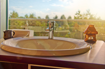 Stylish indoor setting - bathroom sink with a garden view at sun