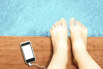 Woman legs with blank screen smartphone at swimming pool - liste