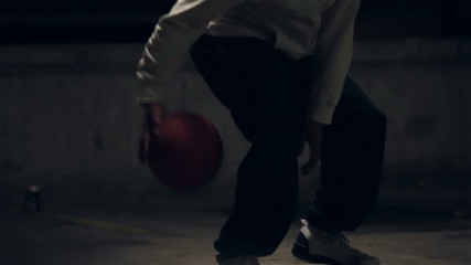Hooded basketball player dribbling the ball at night
