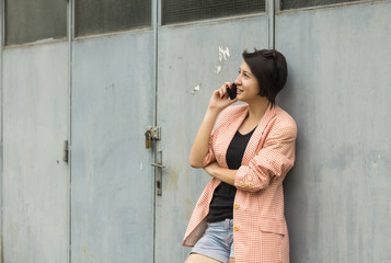 Young woman in front of a garage talking on the phone