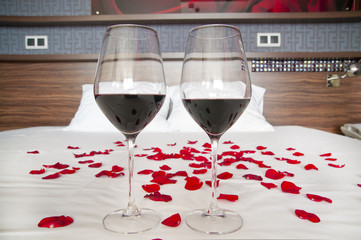 Romantic bedroom - glasses of red wine and rose petals on a bed