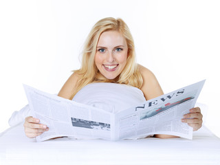 Woman is reading newspaper in bed