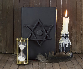 Black magic book with candle and quill