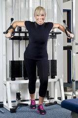 Reife Frau im Fitness Studio an Trainingsgerät Oberkörpertrain