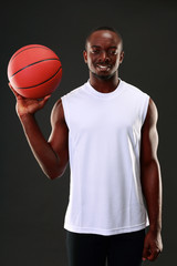 Happy african american basketball player over black background