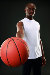 Portrait of african man giving basketball ball at you