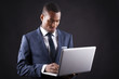 Young business man with a laptop over dark background
