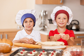 little children making cakes and smiling.