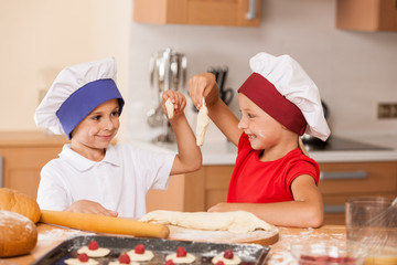 little children making bakery and smiling.