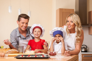 Young parents cooking together with children.
