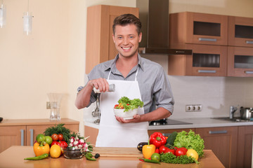 handsome man adding solt to fresh salad.