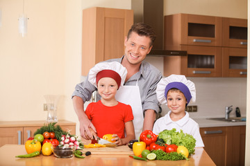 Young father teaching children how to prepare salad.