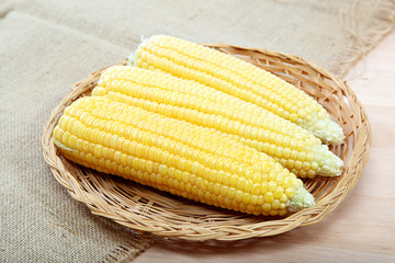 Corn on the cob in a basket on a wooden table.