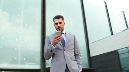 serious businessman with smartphone outdoors