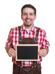 Lachender Mann in Lederhose zeigt Werbetafel