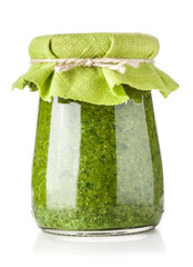 Glass jar of pesto sauce isolated on white